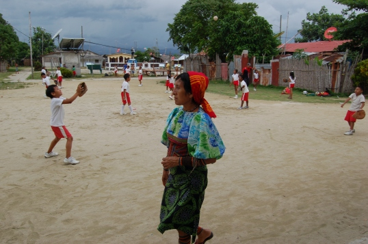 Kuna woman in traditional garb and children playing baseball